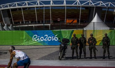 A cyclist rides past military soldiers who are standing guard in front of Olympic Park in the Barra da Tijuca neighborhood ahead of the 2016 Olympic Games in Rio de Janeiro, Brazil, on Sunday, July 24, 2016. Brazil's federal police detained a group of Brazilian nationals on Thursday, July 21, who were allegedly plotting terrorist attacks for the Summer Olympics, which are set to kick off early next month. Photographer: Dado Galdieri/Bloomberg