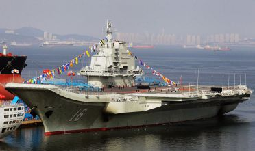 "TO GO WITH China-Japan-maritime-military,ANALYSIS by Sebastien Blanc (FILES) This file photo taken on September 24, 2012 shows China's first aircraft carrier, a former Soviet carrier called the Varyag, docked after its handover to the People's Liberation Army (PLA) navy in Dalian, northeast China's Liaoning province.  China's communist rulers are making waves in the Pacific as they extend their naval strength and reach while Japan and the Philippines bolster their own fleets, increasing the risk of a maritime conflict, analysts say. Beijing's first such vessel, the refitted Soviet-era Liaoning, went into service last autumn, and Song Xue, deputy chief of staff of the navy, said in April, 2013 that ""China will have more than one aircraft carrier"".       CHINA OUT     AFP PHOTO / FILES        (Photo credit should read STR/AFP/Getty Images)"