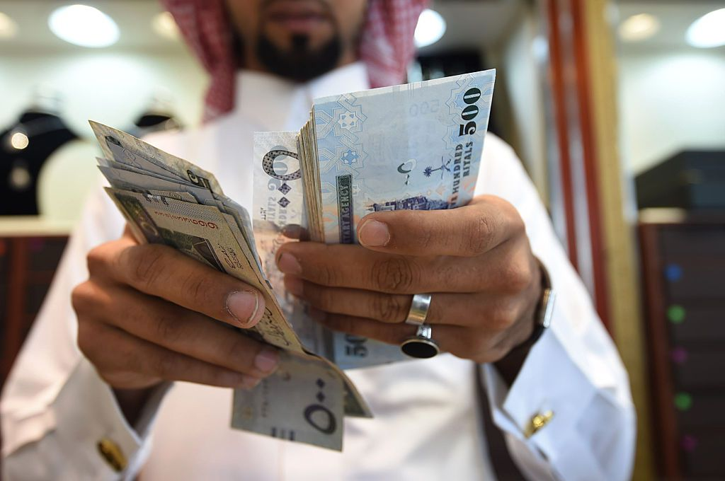 A man counts Saudi riyal banknotes at his jewelry shop in Tiba market in the capital Riyadh on October 3, 2016. / AFP / FAYEZ NURELDINE        (Photo credit should read FAYEZ NURELDINE/AFP/Getty Images)