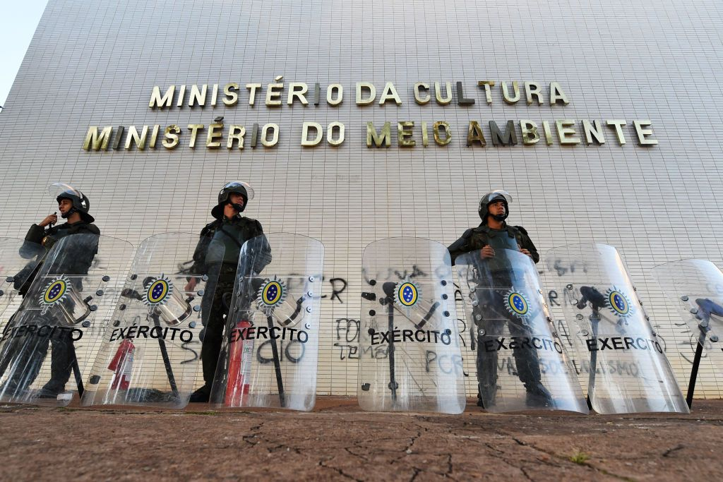 Brazilian Army military police personnel in riot gear guard public buildings in Brasilia, on May 25, 2017. Brazilian soldiers deployed Wednesday to defend government buildings in the capital Brasilia after protesters demanding the exit of President Michel Temer smashed their way into ministries and fought with riot police. / AFP PHOTO / EVARISTO SA        (Photo credit should read EVARISTO SA/AFP/Getty Images)
