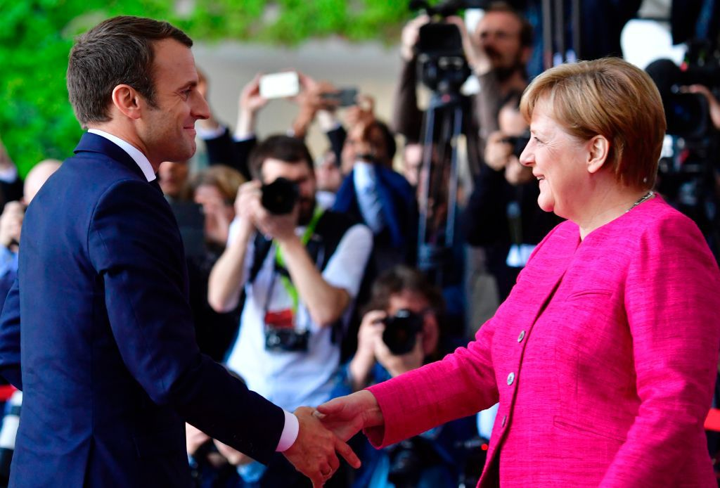 """French President Emmanuel Macron (L) is greeted by German Chancellor Angela Merkel (R) prior to talks at the Chancellery in Berlin on May 15, 2017. France's new President Emmanuel Macron secured backing from key ally Chancellor Angela Merkel for his bid to shake up Europe, despite scepticism in Berlin over his proposed reforms. Travelling to the German capital to meet the veteran leader in his first official trip abroad, Macron used the opportunity to call for a """"historic reconstruction"""" of Europe.  / AFP PHOTO / John MACDOUGALL        (Photo credit should read JOHN MACDOUGALL/AFP/Getty Images)"""
