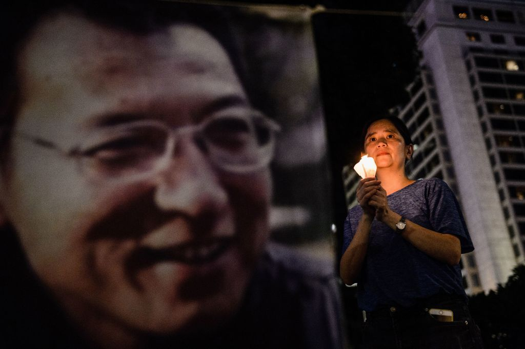"""A woman holds a candle as she attends a vigil for terminally-ill Nobel laureate Liu Xiaobo (pictured on banner) in Hong Kong on June 29, 2017. Liu wants Chinese authorities to let him get treatment abroad, friends say, as officials said his cancer has spread throughout his body. The Nobel Peace Prize winner, who was sentenced to 11 years in prison in 2009 for """"subversion"""" after calling for democratic reforms, was released on medical parole after being diagnosed with terminal liver cancer last month, his lawyer said this week.  / AFP PHOTO / Anthony WALLACE        (Photo credit should read ANTHONY WALLACE/AFP/Getty Images)"""