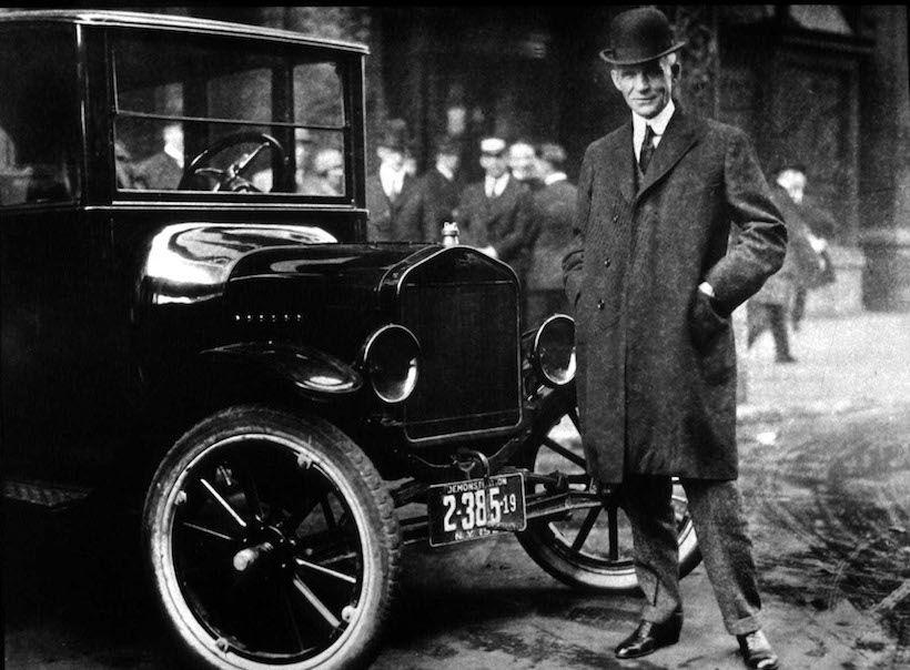 Henry Ford con il Model T, prima autovettura prodotta in serie attraverso l'uso la tecnica della catena di montaggio. (Foto: Getty Images).