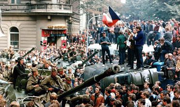 Czech youngsters holding a Czechoslovak flag stand atop an overturned truck as other Prague residents surround Soviet tanks in  Prague on 21 August 1968 as the Soviet-led invasion by the Warsaw Pact armies crushed the so called Prague Spring reform in former Czechoslovakia.        (Photo credit should read LIBOR HAJSKY/AFP/Getty Images)