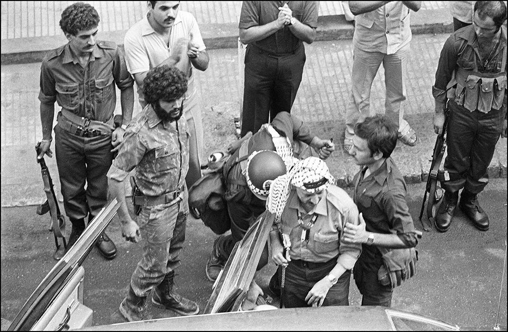 (FILES) Palestine Liberation Organisation (PLO) chairman Yasser Arafat (c-wearing keffieh) is seen in this 30 August 1982 file picture in Beirut, surrounded by heavy security as he leaves the Israeli-occupied city for Tunis. The Lebanese civil war broke out in April 1975 when Palestinians attacked a Maronite Christian leader. In return Christian militia, backed by Christian Kataeb (Phalangist) party, opened fire on a bus loaded with Palestinians, killing most of its passengers. Intercommunal fighting between Christians and Muslim  AFP PHOTO/DOMINIQUE FAGET / AFP PHOTO / AFP FILES / DOMINIQUE FAGET        (Photo credit should read DOMINIQUE FAGET/AFP/Getty Images)