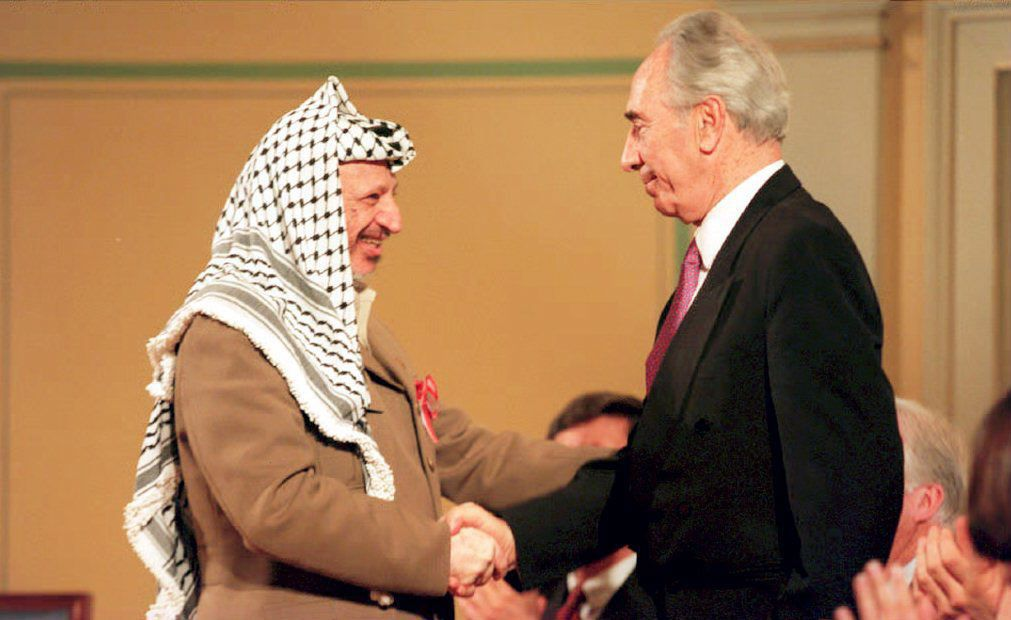 OSLO, NORWAY - MAY 18:  OSLO, NOR - MAY 18:  PLO Chariman Yasser Arafat (L) shakes hands with Israeli Foreign Minister Shimon Peres 18 May 1994 at a ceremony honoring Norway's role in the Israeli-PLO peace accord. Arafat said his recent call for a Moslem holy war was not a call for violence but a call to strive for complete Middle East peace.  (Photo credit should read SCANFOTO/AFP/Getty Images)