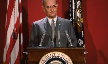 circa 1965:  American statesman Lyndon Baines Johnson (1908 - 1973), the 36th President of the United States of America, making an address at a podium flanked by two flags.  (Photo by Keystone/Getty Images)