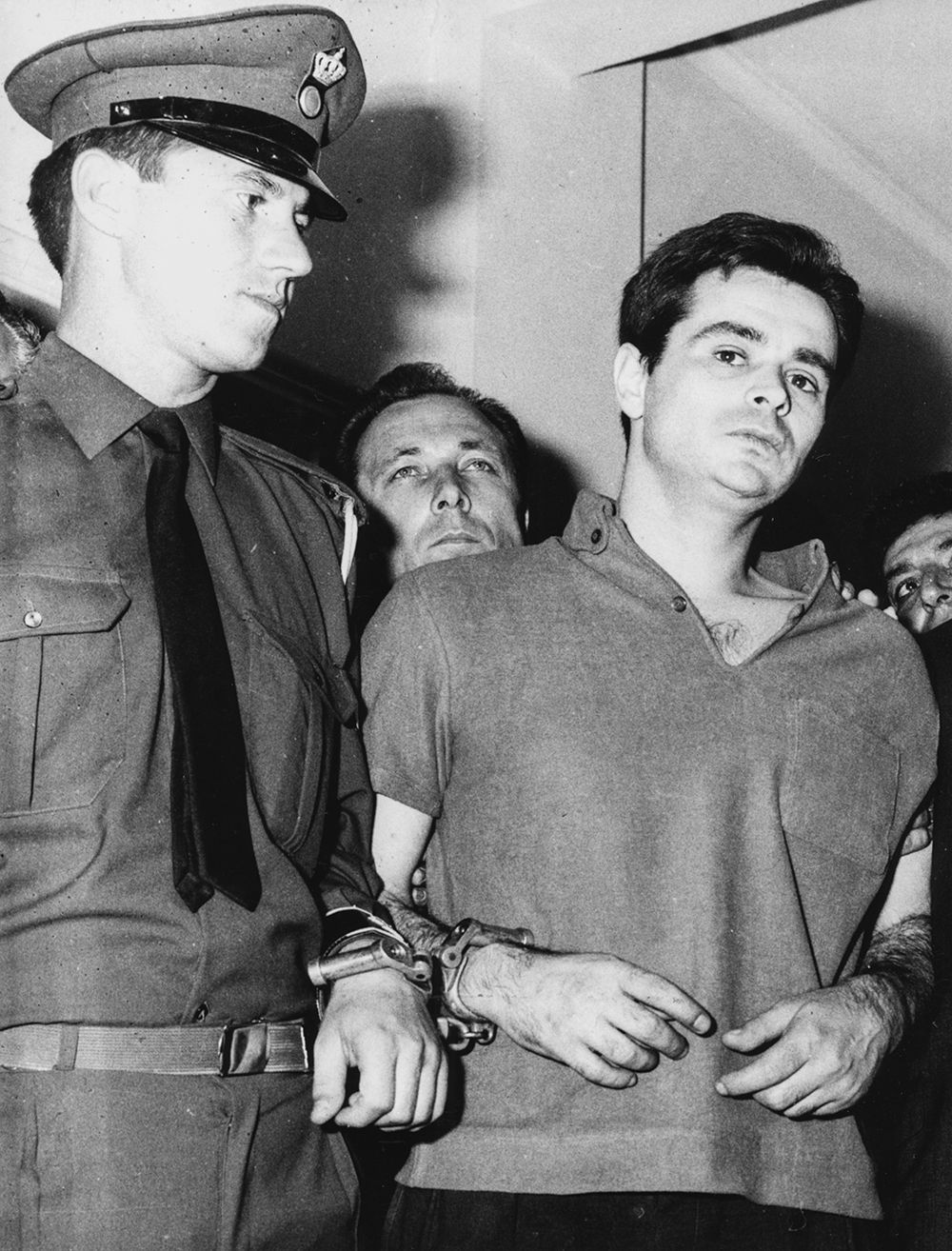 Alexandros Panagoulis being led away by an officer in military court after being sentenced to death for his assassination attempt on George Papadopoulos, 1968. Printed following the funeral of Alexandros Panagoulis after his death in a car crash on May 10th 1976. (Photo by Keystone/Hulton Archive/Getty Images)