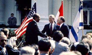 Il presidente egiziano Anwar al-Sadat (sinistra), quello americano Jimmi Carter (centro) e il premier israeliano Menachem Begin (destra)  durante la firma degli Accordi di Camp David, 1979. (Foto: AFP/Getty Images).