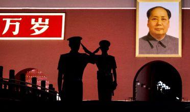 Cambio della guardia tra due soldati di fronte a un ritratto di Mao Zedong in piazza Tiananmen (Foto: Kevin Frayer/Getty Images).