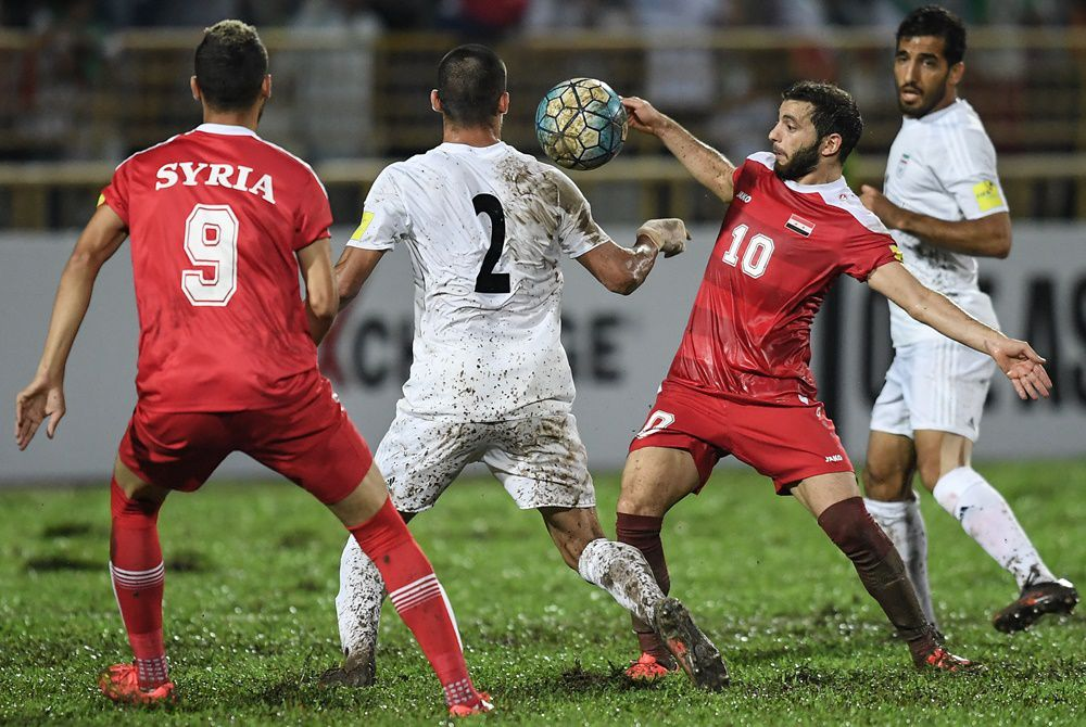 Mahmoud Almawas of Syria (2nd R) fights for the ball with Milad Mohammadi of Iran (2nd L) during the 2018 World Cup qualifying football match between Syria and Iran at Tuanku Abdul Rahman Stadium in Seremban on November 15, 2016. / AFP / MOHD RASFAN (Photo credit should read MOHD RASFAN/AFP/Getty Images)