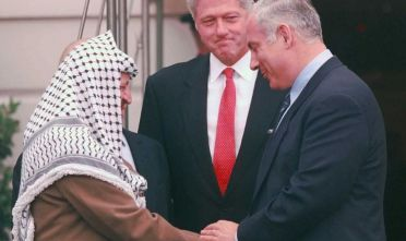 Bill Clinton, Yasser Arafat e Benjamin Netanyahu durante la firma del memorandum di Wye River (Foto: PAUL J. RICHARDS/AFP/Getty Images).