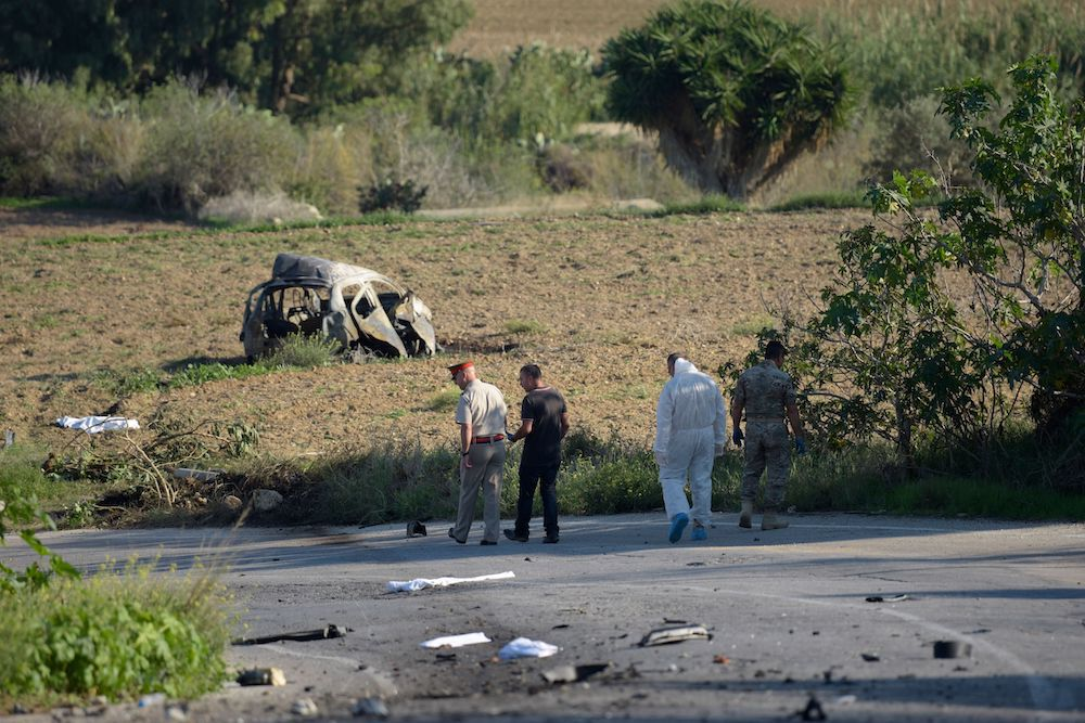 TOPSHOT - Police and forensic experts inspect the wreckage of a car bomb believed to have killed journalist and blogger Daphne Caruana Galizia close to her home in Bidnija, Malta, on October 16, 2017. The force of the blast broke her car into several pieces and catapulted the journalist's body into a nearby field, witnesses said. She leaves a husband and three sons. Caruana Galizia's death comes four months after Prime Minister Joseph Muscat's Labour Party won a resounding victory in a general election he called early as a result of scandals to which Caruana Galizia's allegations were central.  / AFP PHOTO / STR / Malta OUT        (Photo credit should read STR/AFP/Getty Images)
