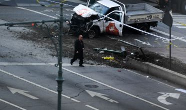 "An investigator walks past a crashed pickup truck following an incident in New York on October 31, 2017.   A pickup driver killed eight people in New York on Tuesday, mowing down cyclists and pedestrians, before striking a school bus in what officials branded a ""cowardly act of terror."" Eleven others were seriously injured in the broad daylight assault and first deadly terror-related attack in America's financial and entertainment capital since the September 11, 2001 Al-Qaeda hijackings brought down the Twin Towers.  / AFP PHOTO / Don EMMERT        (Photo credit should read DON EMMERT/AFP/Getty Images)"