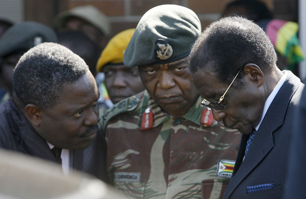 The head of Zimbabwe Central Intelligence Organisation (CIO) Happyton Bonyongwe (L) with Constantine Chiwenga, the commander of the Zimbabwean Army (C) are pictured with President Robert Mugabe at Harare Airport, on July 03, 2008.  Robert Mugabe said he is only open to negotiations on an end to Zimbabwe's political crisis if he is accepted as the country's president. On July 03, the United States pushed for a UN travel ban and an assets freeze on Mugabe and 13 of his cronies in protest at the presidential runoff vote.  AFP PHOTO / ALEXANDER JOE (Photo credit should read ALEXANDER JOE/AFP/Getty Images)