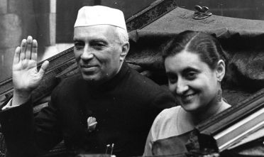 July 1956:  India's first Prime Minister Jawaharlal Nehru (1869 - 1964), with his daughter Indira Gandhi (born Indira Priyardarshini Nehru, 1917 - 1984) future Prime Minister. They are being driven through the streets of London after the Freedom of the City of London was bestowed on Nehru at the Guild Hall.  (Photo by Monty Fresco/Topical Press Agency/Getty Images)