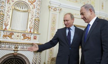 Russian President Vladimir Putin (L) shows the way to Israeli Prime Minister Benjamin Netanyahu during a meeting at the Novo-Ogaryovo residence, outside Moscow, on September 21, 2015. AFP PHOTO / POOL / IVAN SEKRETAREV        (Photo credit should read IVAN SEKRETAREV/AFP/Getty Images)