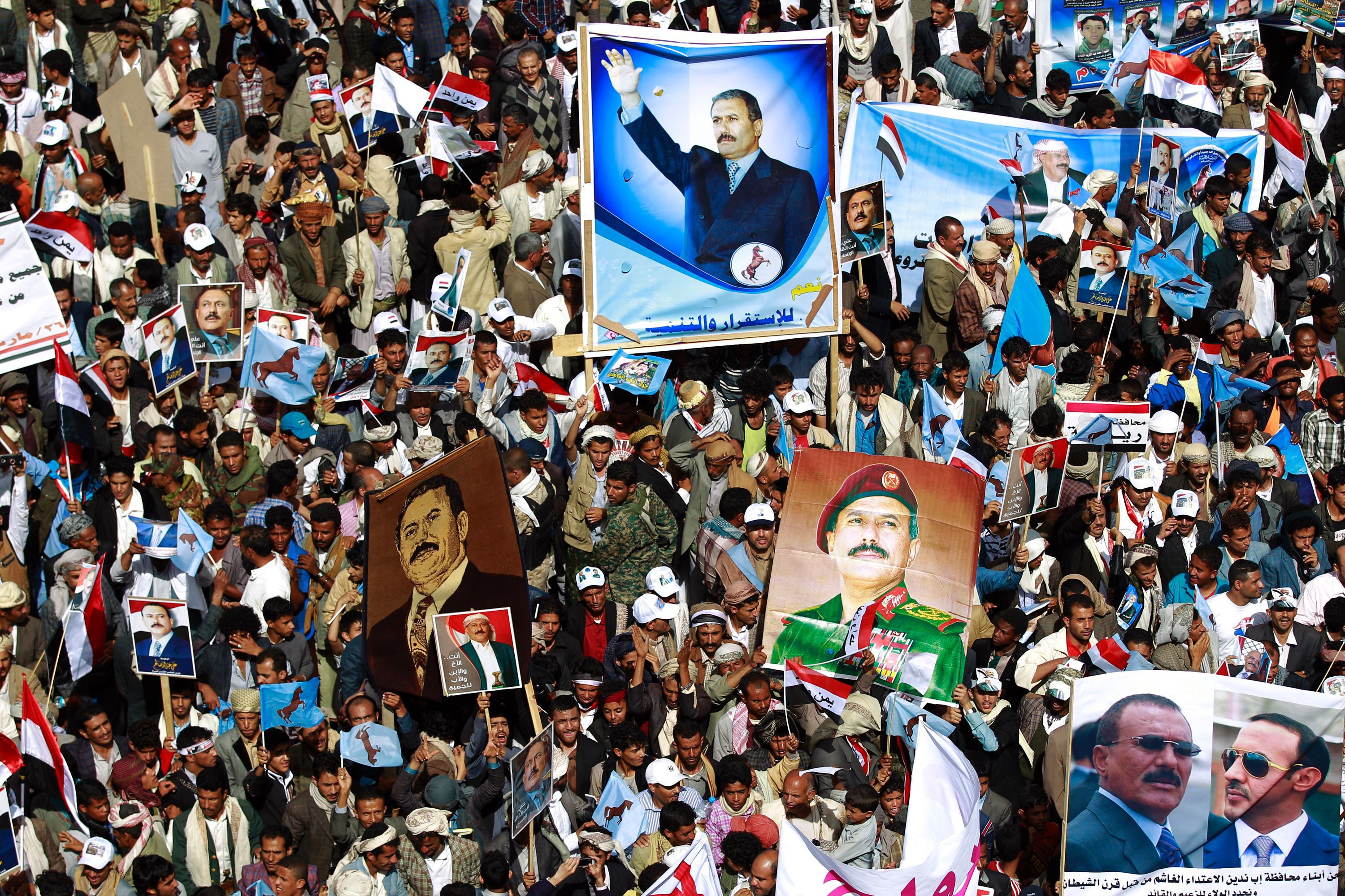 TOPSHOT - Yemenis hold placards bearing portraits of former president Ali Abdullah Saleh during a protest against the Saudi-led coalition, commemorating one year of the alliance's military campaign against insurgents on March 26, 2016 next to the Monument to the Unknown Soldier in the Yemeni capital Sanaa. The protest was called for by the General People's Congress, the party of rebel-allied former president Ali Abdullah Saleh, who appeared briefly at the rally, an AFP photographer said. The military intervention that began on March 26 last year has yet to deal a decisive blow to the Iran-backed rebels, who continue to control the capital and large parts of the country.   / AFP / MOHAMMED HUWAIS        (Photo credit should read MOHAMMED HUWAIS/AFP/Getty Images)