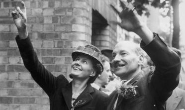 Newly-elected British prime minister Clement Attlee (1883 - 1967) and his wife Violet wave to the crowds during a visit to the Labour Party headquarters in Transport House, Westminster, 26th July 1945. (Photo by William Vanderson/Fox Photos/Hulton Archive/Getty Images)