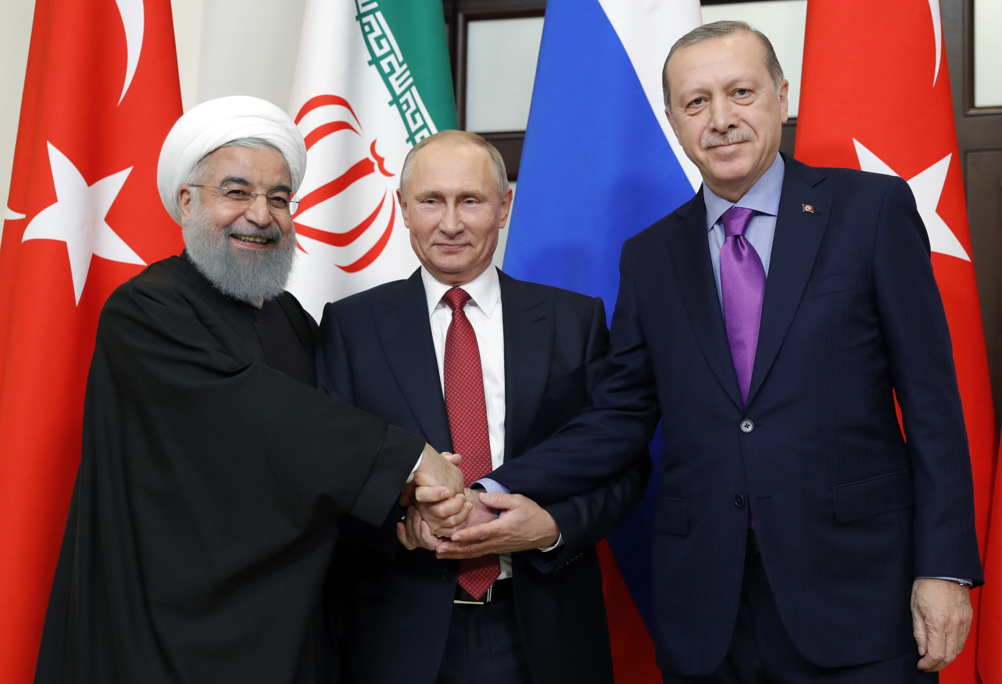 TOPSHOT - Russian President Vladimir Putin (C), Turkish President Recep Tayyip Erdogan (R) and Iranian President Hassan Rouhani pose during a trilateral meeting on Syria in Sochi on November 22, 2017. / AFP PHOTO / SPUTNIK / Mikhail METZEL (Photo credit should read MIKHAIL METZEL/AFP/Getty Images)