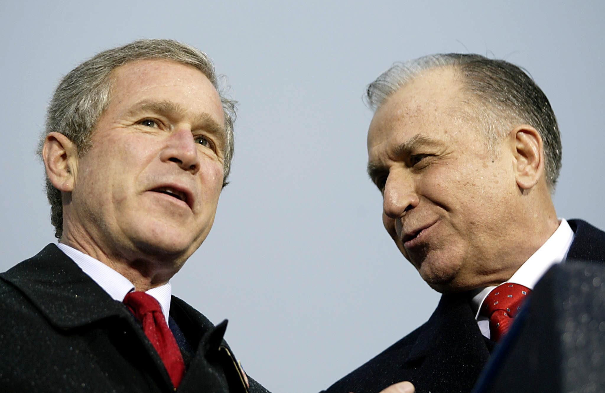 BUCHAREST, ROMANIA: US President George W. Bush (L) speaks with Romanian Prtesident Ion Iliescu at a rally at the Piata Revolutiei n Bucharest 23 November 2002. Bush attended a two-day NATO summit in Prague in the Czech Republic 21 and 22 November where NATO voted to expand and include Romania. AFP Photo/Stephen JAFFE (Photo credit should read STEPHEN JAFFE/AFP/Getty Images)