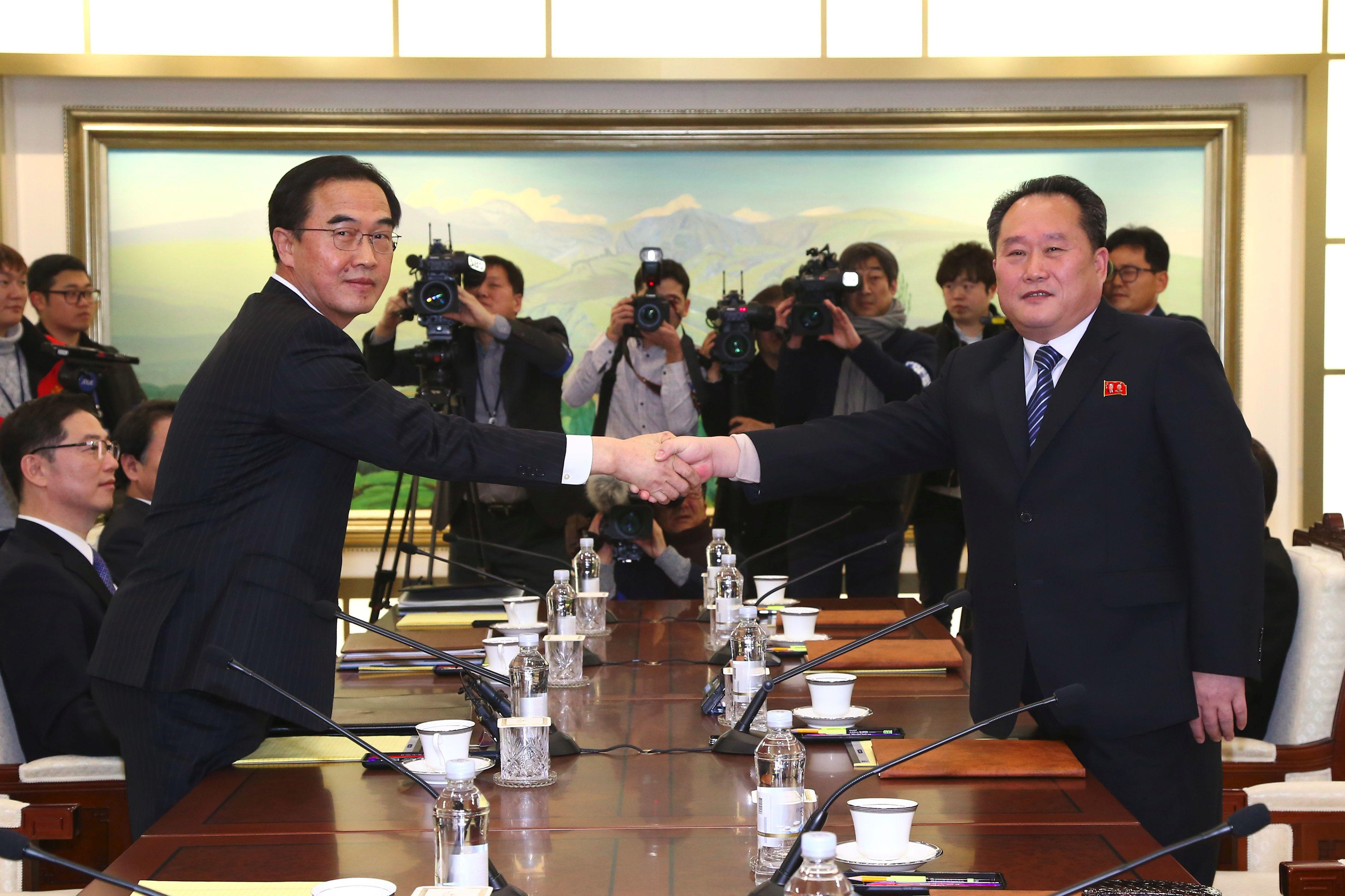 Il ministro sudcoreano Cho Myung-Gyun (sinistra) si stringe la mano con il delegato nordcoreano Ri Son-Gwon (destra) durante l'incontro al villaggio di confine di Panmunjom nella zona demilitarizzata (DMZ) che divide le due Coree il 9 gennaio 2018. (Foto di: KOREA POOL/AFP/Getty Images)