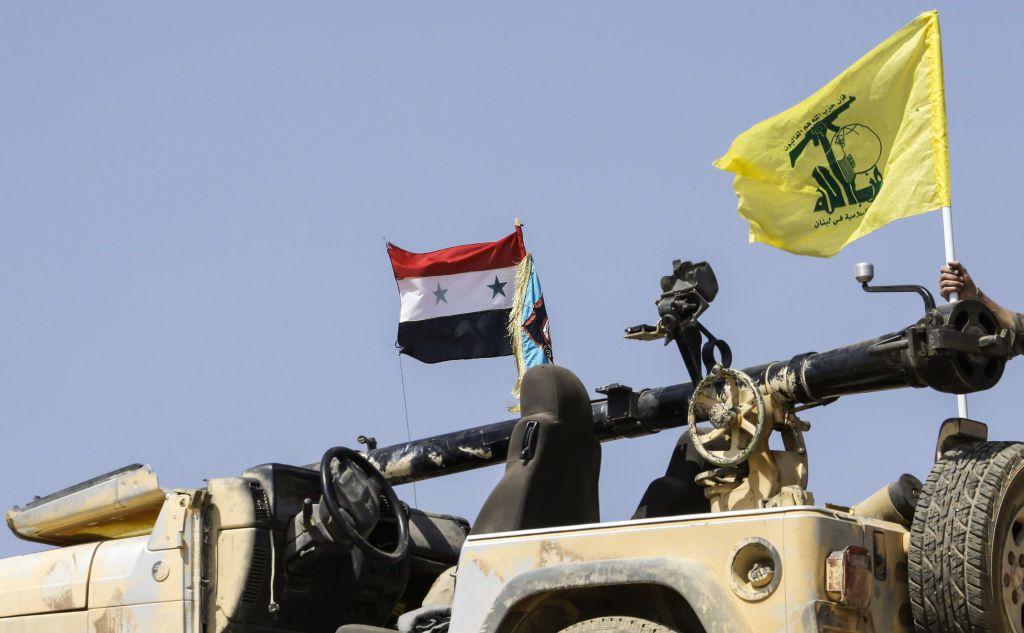 La bandiera siriana e il vessillo giallo di Hezbollah campeggiano su un veicolo da guerra impiegato nei combattimenti nella città siriana di Flita nei pressi del confine con il Libano.       Foto di: LOUAI BESHARA/AFP/Getty Images