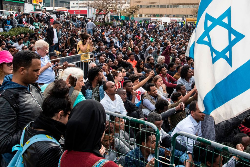African migrants and Israeli activists demonstrate outside the Embassy of Rwanda in the Israeli city of Herzliya on February 7, 2018, against the Israeli government's policy to forcibly deport African refugees and asylum seekers to Rwanda and Uganda. Israel began on January 3 implementing a plan to deport by April tens of thousands of African migrants, mainly Eritreans and Sudanese, who entered the country illegally, threatening to arrest those who stay. Israel tacitly recognises that the Sudanese and Eritreans cannot be returned to their dangerous homelands, so it has signed deals with Rwanda and Uganda, which agree to accept departing migrants on condition they consent to the arrangement, activists say. / AFP PHOTO / JACK GUEZ        (Photo credit should read JACK GUEZ/AFP/Getty Images)