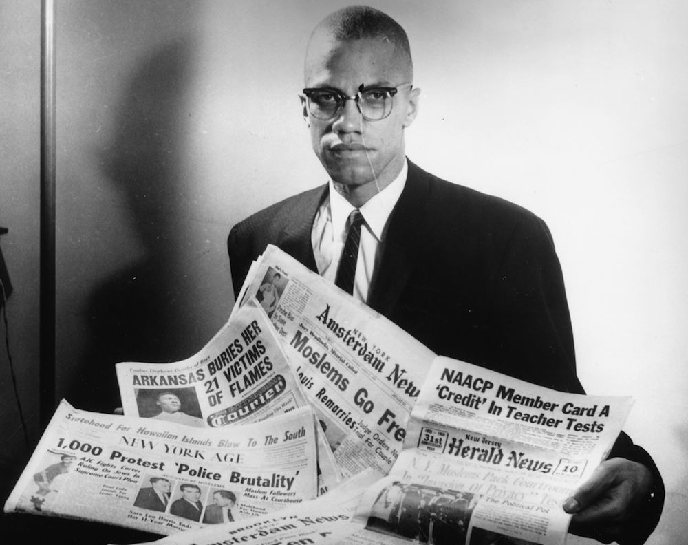 Portrait of human rights activist Malcolm X reading stories about himself in a pile of newspapers, circa 1963. (Photo by Three Lions/Hulton Archive/Getty Images)
