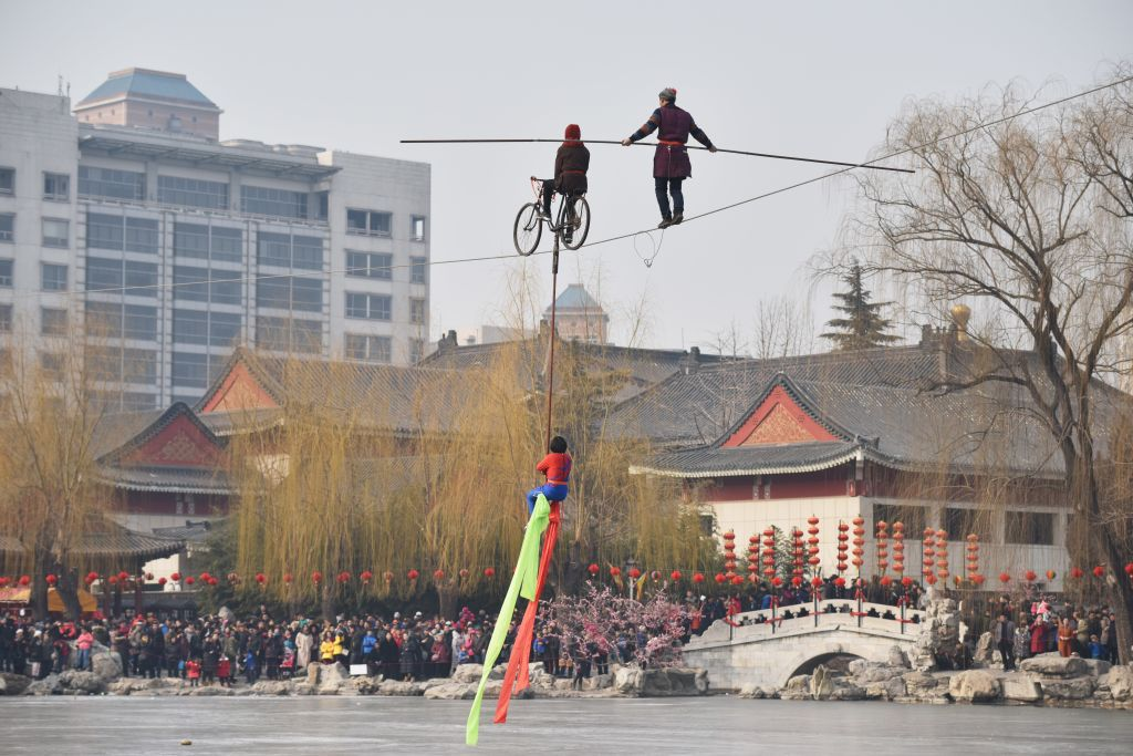 Wire walkers perform at a Lunar New Year temple fair in Beijing on February 19, 2018. China is in the midst of a week-long holiday marking the beginning of the Year of the Dog. / AFP PHOTO / GREG BAKER        (Photo credit should read GREG BAKER/AFP/Getty Images)