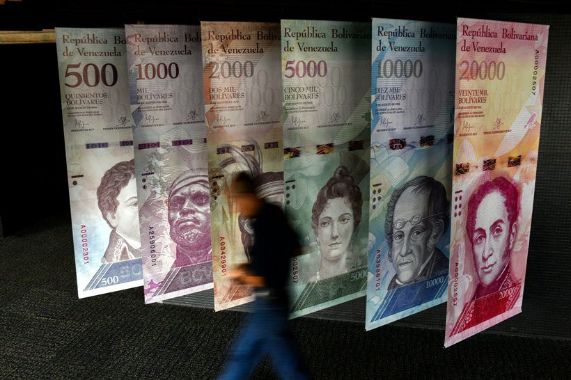 """TOPSHOT - A man walks past banners showing banners depicting Venezuela's currency, the Bolivar, at the Central Bank of Venezuela (BCV) in Caracas on January 31, 2018. Venezuelan President Nicolas Maduro signed the proposal of a new digital currency called """"Petro"""" to try to combat the economic crisis. / AFP PHOTO / FEDERICO PARRA        (Photo credit should read FEDERICO PARRA/AFP/Getty Images)"""