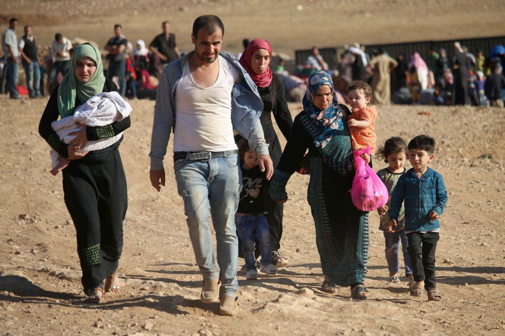Rifugiati siriani ritornano in Siria dopo aver attraversato il confine giordano vicino alla città di Nasib lo scorso agosto. Foto di: MOHAMAD ABAZEED/AFP/Getty Images