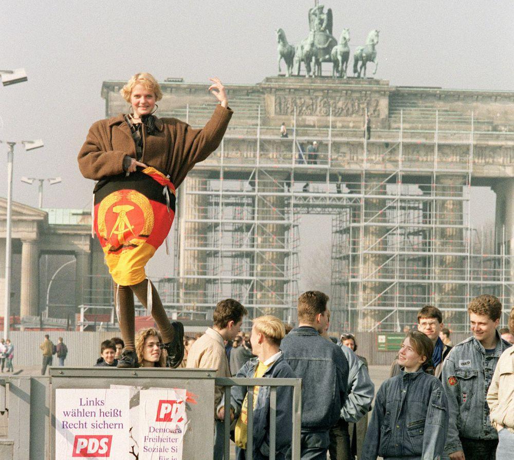 Una ragazza avvolta da una bandiera della DDR davanti la porta di Brandeburgo di Berlino, pochi giorni prima delle elezioni in Germania Est (Foto: PATRICK HERTZOG/AFP/Getty Images).