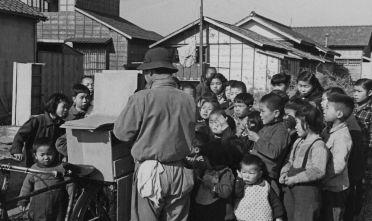 Un gruppo di bambini burakumin che guarda uno show di burattini kamishibai durante l'occupazione americana del Giappone, 1950. (Foto: Horace Bristol/Three Lions/Hulton Archive/Getty Images).