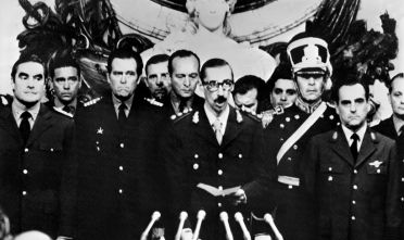 General Orlando Ramon Agosti (R) and Admiral Emilio Massera (L) stand as Lieutenant General Jorge Rafael Videla (C), President of Argentina, after takes an oath as 38th President Argentinian Republic, 29 March 1976, in Buenos Aires. Following a military coup against Isabel Perone, Videla became President, 28 March 1976, as head of three-man military junta including General Agosti and Admiral Massera. Videla retired in 1981 and was succeeded by General Roberto Viola. In 1977, American sources reported 6,000 capital executions and from 12,000 to 17,000 people jailed. Condemned to a life term sentence, Videla was pardoned by President Carlos Menem and released, 30 December 1990. Fotografia tomada en Buenos Aires, el 29 de marzo de 1976 del general Jorge Rafael Videla (C) en momentos en que jura como presidente de la Argentina, luego del golpe de estado militar del 24 de marzo de 1976. A la izquierda esta el almirante Eduardo Emilio Massera y a la derecha el brigadier Orlando Ramon Agosti. A 26 anos del golpe de estado, las heridas dejadas por la ultima dictadura militar (1976-83) no han podido cicatrizar y la sociedad sigue clamando por verdad y justicia. (Photo credit should read OFF/AFP/Getty Images)