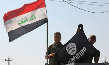 Members of the Iraqi forces hold an upside down Islamic State (IS) group flag in the northern Iraqi town of Sharqat on September 22, 2017, after ousting the jihadists from the town.  Iraqi forces achieved the first goal of a new offensive against the Islamic State group on just its second day, penetrating the northern town of Sharqat, AFP correspondents said. / AFP PHOTO / AHMAD AL-RUBAYE        (Photo credit should read AHMAD AL-RUBAYE/AFP/Getty Images)