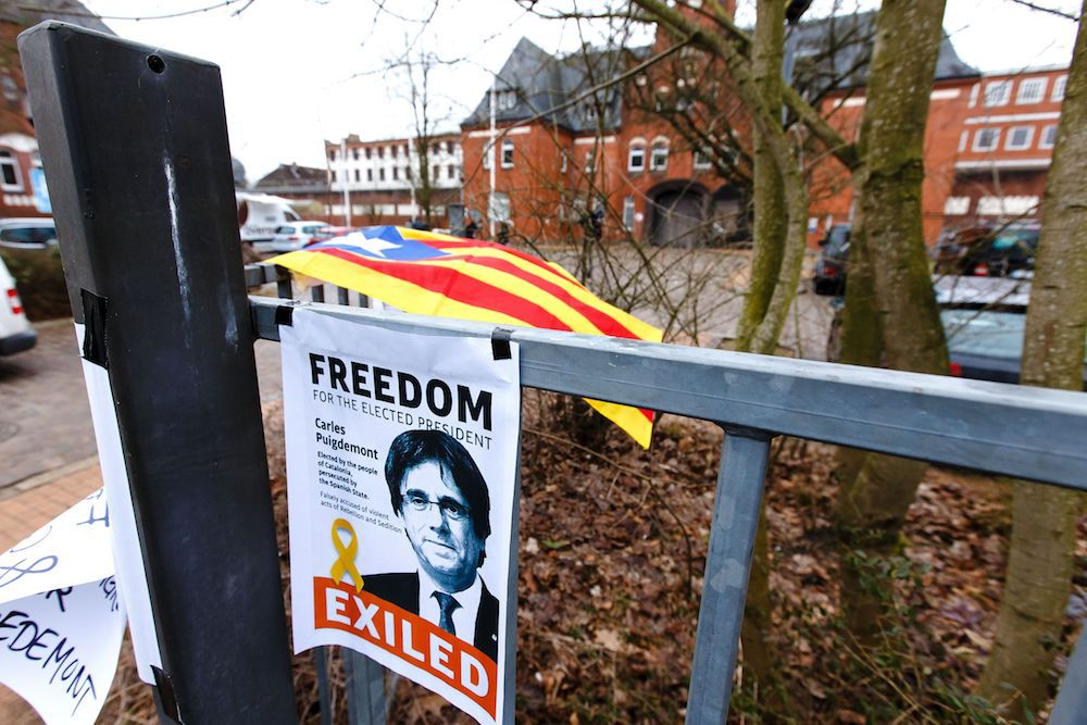 """A poster with the slogan """"Freedom for the elected president"""" is attached to a fence in front of the prison (Justizvollzugsanstalt - JVA) of Neumuenster, northern Germany, where former Catalan regional president Carles Puigdemont is detained, on March 28, 2018. Former Catalan president Carles Puigdemont, in German custody since March 25, 2018 and pending possible extradition to Spain to face """"rebellion"""" charges, vows to """"never surrender"""" in his fight for regional independence, his lawyer said March 27. / AFP PHOTO / dpa / Frank Molter / Germany OUT        (Photo credit should read FRANK MOLTER/AFP/Getty Images)"""