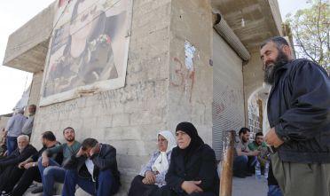 Civili siriani al checkpoint di Wafideen alla periferia di Damasco al confine con la Ghuta il 3 aprile scorso, mentre le forze siriane procedevano nella loro occupazione della regione prima in mano ai miliziani anti-regime. Foto di: LOUAI BESHARA/AFP/Getty Images