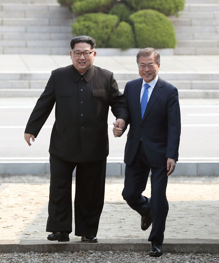 PANMUNJOM, SOUTH KOREA - APRIL 27:  North Korean Leader Kim Jong Un (L) and South Korean President Moon Jae-in (R) cross back the military demarcation line after Moon crossing the border to the north side upon meeting for the Inter-Korean Summit on April 27, 2018 in Panmunjom, South Korea. Kim and Moon meet at the border today for the third-ever inter-Korean summit talks after the 1945 division of the peninsula, and first since 2007 between then President Roh Moo-hyun of South Korea and Leader Kim Jong-il of North Korea.  (Photo by Korea Summit Press Pool/Getty Images)