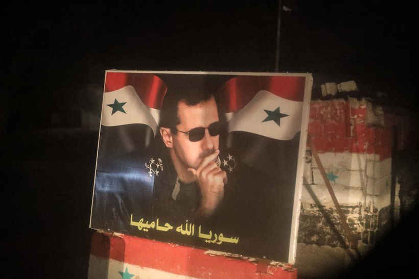 Un poster di Bashar al-Asad fotografato da un pullman che trasporta ribelli e civili fuori da Duma. Foto di ABDULLAH HAMMAM/AFP/Getty Images