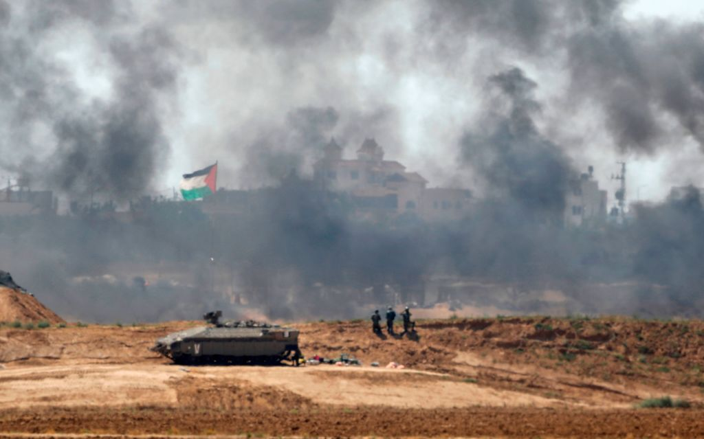 A picture taken on May 15, 2018 near the Kibbutz of Nir Oz on the border with the southern Gaza strip shows Israeli soldiers standing near a Namer armoured personnel carrier (APC) along the border through the smoke fumes billowing from tire fires horizon in the Palestinian village of Khuzaa. (Photo by Menahem KAHANA / AFP)        (Photo credit should read MENAHEM KAHANA/AFP/Getty Images)