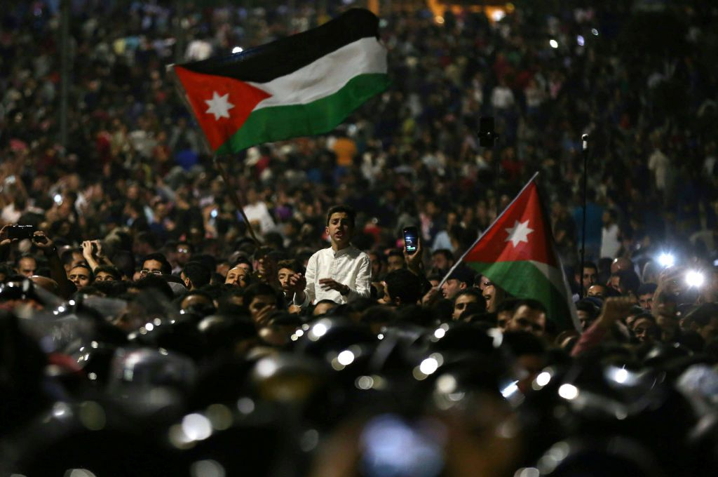 Protesters wave flags near Jordanian security forces during a demonstration outside the prime minister's office in the capital Amman late on June 3, 2018. - Jordan's senate met on June 3 for a special session after another night of protests across the country against IMF-backed austerity measures including a draft income tax law and price hikes. Some 3,000 people faced down a heavy security presence to gather near the prime minister's office in Amman until the early hours of Sunday morning. (Photo by Khalil MAZRAAWI / AFP)        (Photo credit should read KHALIL MAZRAAWI/AFP/Getty Images)