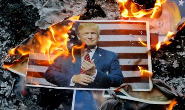 TOPSHOT - A portrait of US President Donald Trump burns during a demonstration in the capital Tehran on December 11, 2017 to denounce his declaration of Jerusalem as Israel's capital.  / AFP PHOTO / ATTA KENARE        (Photo credit should read ATTA KENARE/AFP/Getty Images)