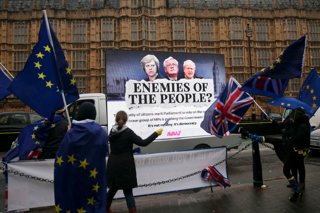 """Pro-EU anti-Brexit demonstrators wave EU and Union Flags as a billboard depicting Britain's Prime Minister Theresa May, Britain's Secretary of State for Exiting the European Union (Brexit Minister) David Davis and Britain's Foreign Secretary Boris Johnson for a campaign by the organisation Avaaz calling for Parliament to have a meaningful vote on the terms of Brexit is driven past outside the Houses of Parliament in central London on December 13, 2017 while MPs debate the EU Withdrawl Bill.  British Prime Minister Theresa May was December 13 facing a rebellion from her own MPs over whether parliament will have a """"meaningful vote"""" on the final Brexit deal in what would be a damaging defeat. / AFP PHOTO / Daniel LEAL-OLIVAS        (Photo credit should read DANIEL LEAL-OLIVAS/AFP/Getty Images)"""