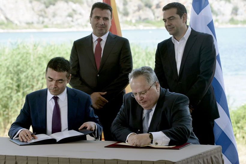 TOPSHOT - Greek Foreign Minister Nikos Kotzias (down, R) and his Macedonian counterpart Nikola Dimitrov (down, L) sign a preliminary accord as Greek Prime Minister Alexis Tsipras (R) and Macedonian Prime Minister Zoran Zaesign stand during a ceremony at Prespes Lake on June 17, 2018. - The foreign ministers of Greece and Macedonia on June 17, 2018 signed a historic preliminary accord to end a 27-year bilateral row by renaming the small Balkan nation the Republic of North Macedonia. (Photo by SAKIS MITROLIDIS / AFP)        (Photo credit should read SAKIS MITROLIDIS/AFP/Getty Images)