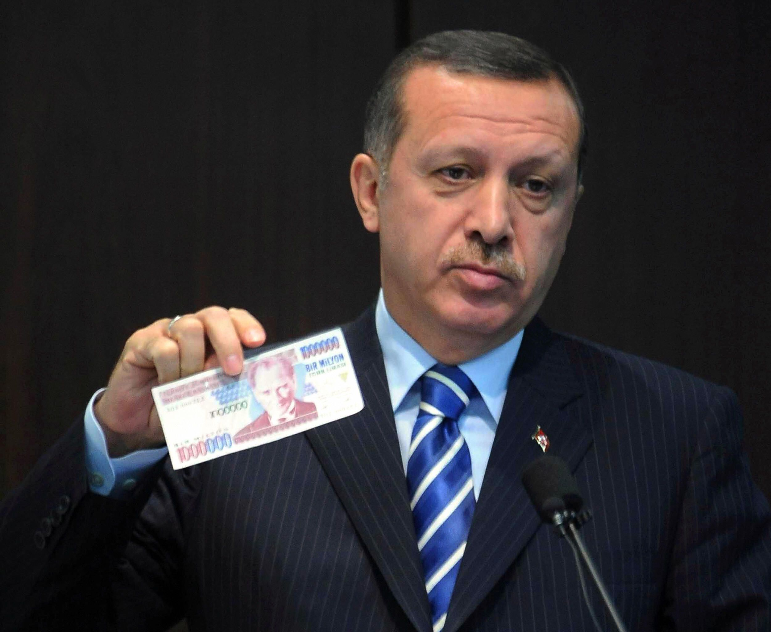"Turkish Prime Minister Tayyip Erdogan displays an banknote of the old Turkish Lira at a news conference in Ankara October 3, 2008. Turkey will return to its old currency, the Turkish Lira, on January 1, after a major money reform four years ago that saw the introduction of the New Turkish Lira. The banner in the background reads ""The Turkish lira is coming"". AFP PHOTO/ADEM ALTAN (Photo credit should read ADEM ALTAN/AFP/Getty Images)"
