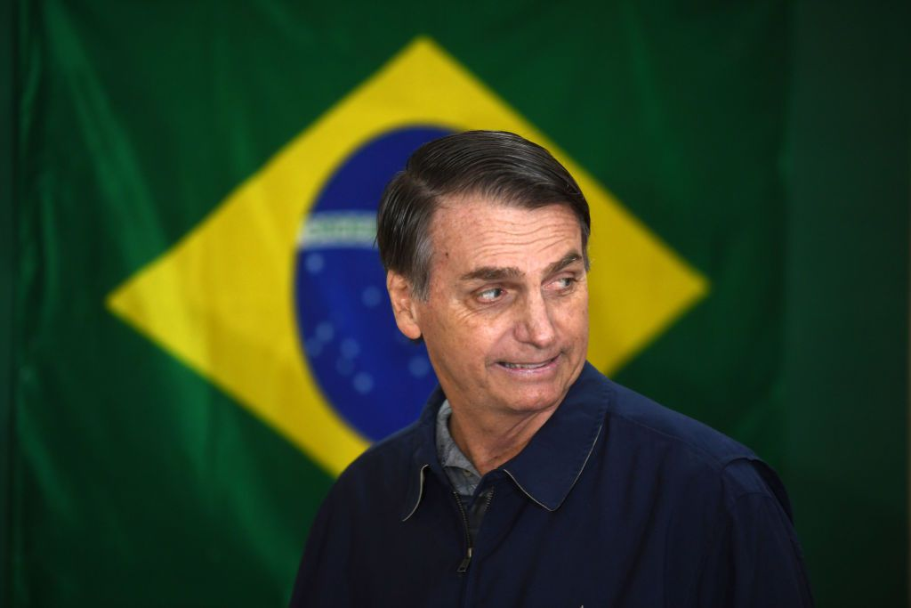 Brazil's right-wing presidential candidate for the Social Liberal Party (PSL) Jair Bolsonaro walks in front of the Brazilian flag as he prepares to cast his vote during the general elections, in Rio de Janeiro, Brazil, on October 7, 2018. - Polling stations opened in Brazil on Sunday for the most divisive presidential election in the country in years, with far-right lawmaker Jair Bolsonaro the clear favorite in the first round. About 147 million voters are eligible to cast ballots and choose who will rule the world's eighth biggest economy. New federal and state legislatures will also be elected. (Photo by Mauro PIMENTEL / AFP)        (Photo credit should read MAURO PIMENTEL/AFP/Getty Images)