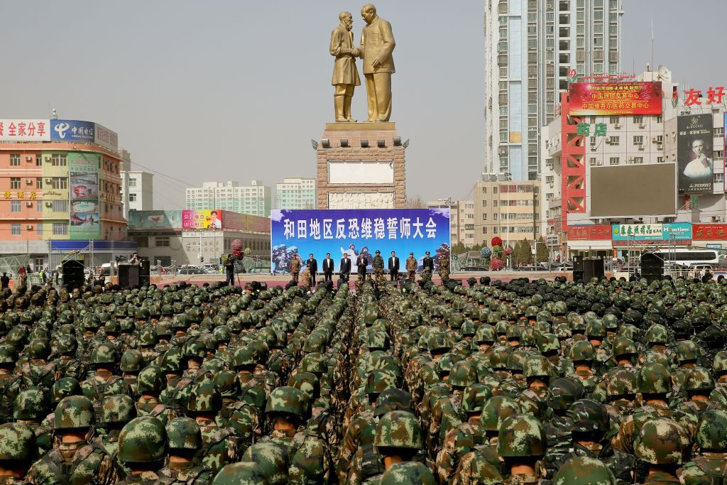 "TOPSHOT - This photo taken on February 27, 2017 shows Chinese military police attending an anti-terrorist oath-taking rally in Hetian, northwest China's Xinjiang Uighur Autonomous Region.  Islamic State militants from China's Uighur ethnic minority have vowed to return home and ""shed blood like rivers"", according to a jihadist-tracking firm, in what experts said marked the first IS threat against Chinese targets. The threat came in a half-hour video released on February 27 by a division of the Islamic State in western Iraq and featuring militants from China's Uighur ethnic group, said the US-based SITE Intelligence Group, which analysed the footage. / AFP PHOTO / STR / China OUT        (Photo credit should read STR/AFP/Getty Images)"