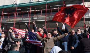 Albanian opposition supporters wave their national flag and a US flag during a protest outside the government building, demanding the resignation of the Albanian prime minister, on February 16, 2019, in Tirana. - Following a series of accusations for corruption and vote buying, the opposition demands the resignation of  Prime Minister Edi Rama and the formation of a technical government that would prepare the groundwork for free and fair elections and severe ties with organized crime. (Photo by Gent SHKULLAKU / AFP)        (Photo credit should read GENT SHKULLAKU/AFP/Getty Images)