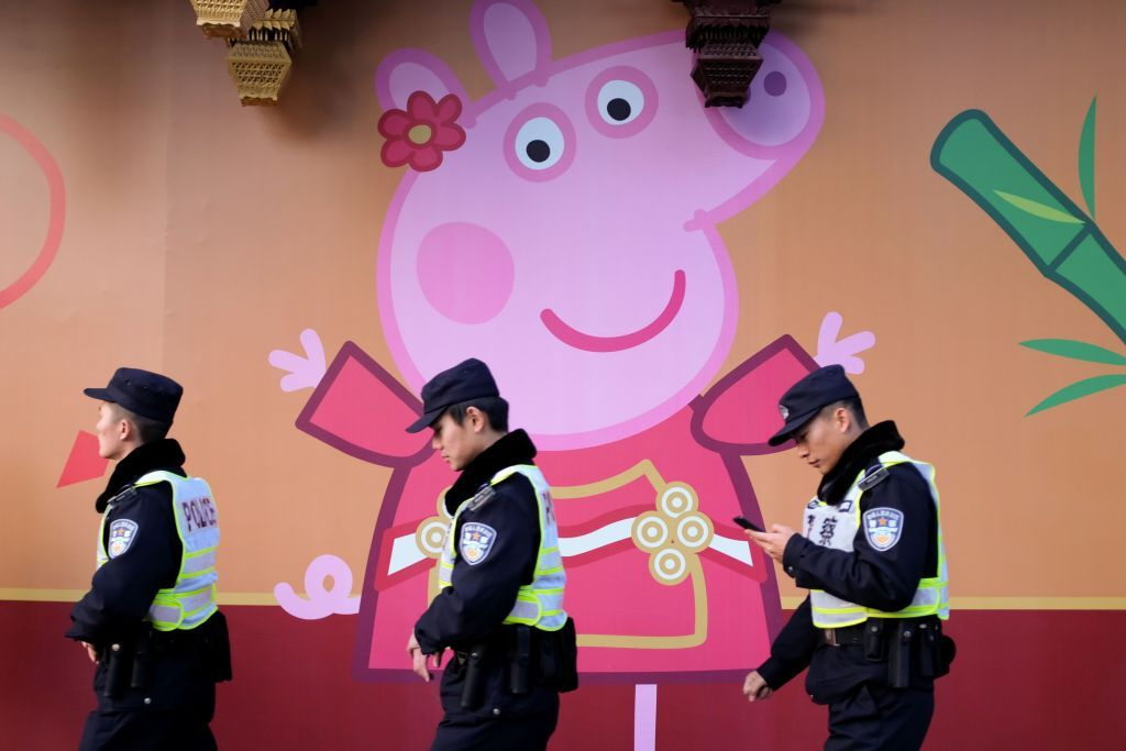 TOPSHOT - This picture taken on January 25, 2019 shows police walking past a Peppa Pig figure on a wall outside the Yu Yuan gardens, a popular tourist spot hosting a 'Peppa Pig pop-up shop' featuring interactive games for children, in Shanghai. - Roasted as a subversive symbol and chopped from a video streaming website in China, it seemed Peppa Pig, the loveable but imperious British cartoon character, faced a bleak future in the Communist-led country. But her popularity has risen unabated, and now just months after state media slammed her as an emblem of the counterculture, she is playing a starring role as the country ushers in the Year of the Pig on February 5. (Photo by Matthew KNIGHT / AFP) / TO GO WITH China-NewYear-Peppa-holiday-cartoon, FEATURE by Poornima WEERASEKARA        (Photo credit should read MATTHEW KNIGHT/AFP/Getty Images)